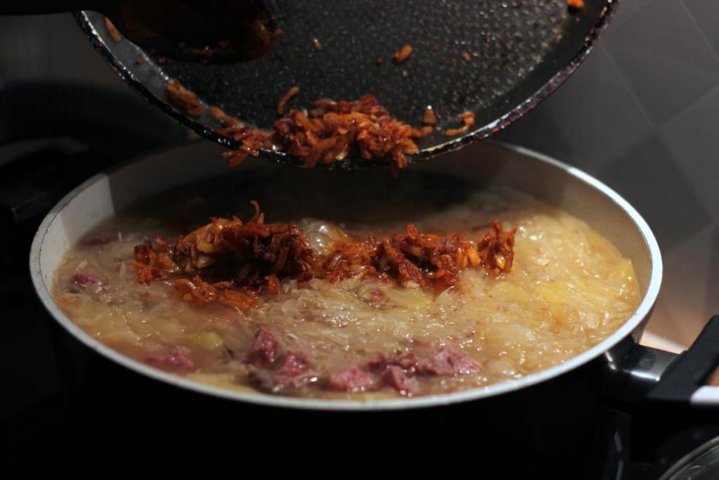 Wrzucanie cebuli z przyprawami do garnka