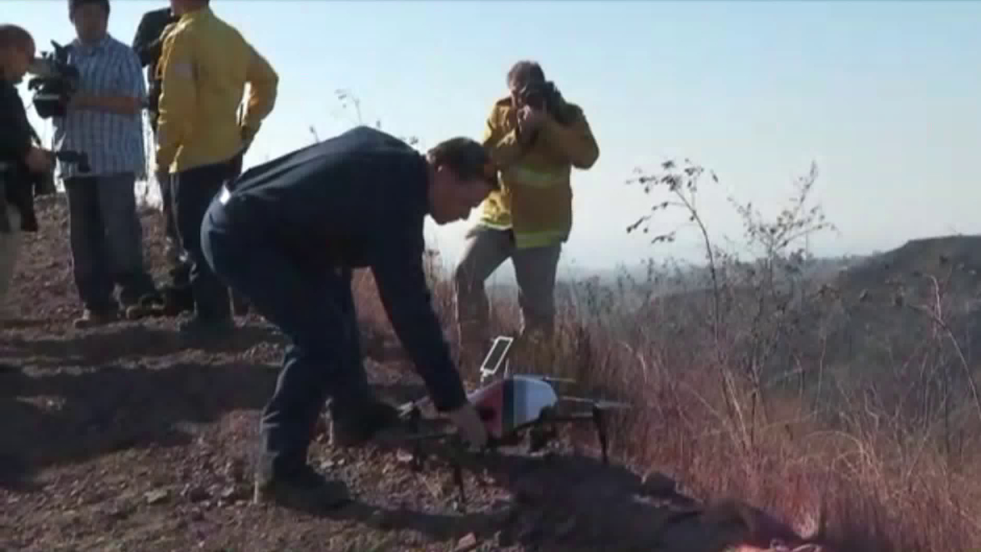 Los Angeles Fire Department officials display one of the agency's drones on Dec. 14, 2017, in Bel-Air, near where the Skirball Fire burned. (Credit: KTLA)