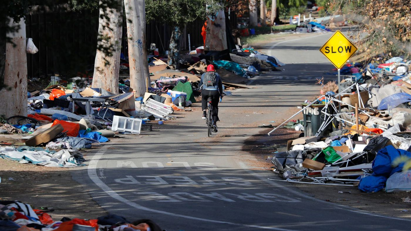 A bicyclist rides past piles of trash from the Santa Ana River homeless camp after it was cleared and more than 700 people relocated in Anaheim in February. (Credit: Allen J. Schaben / Los Angeles Times)