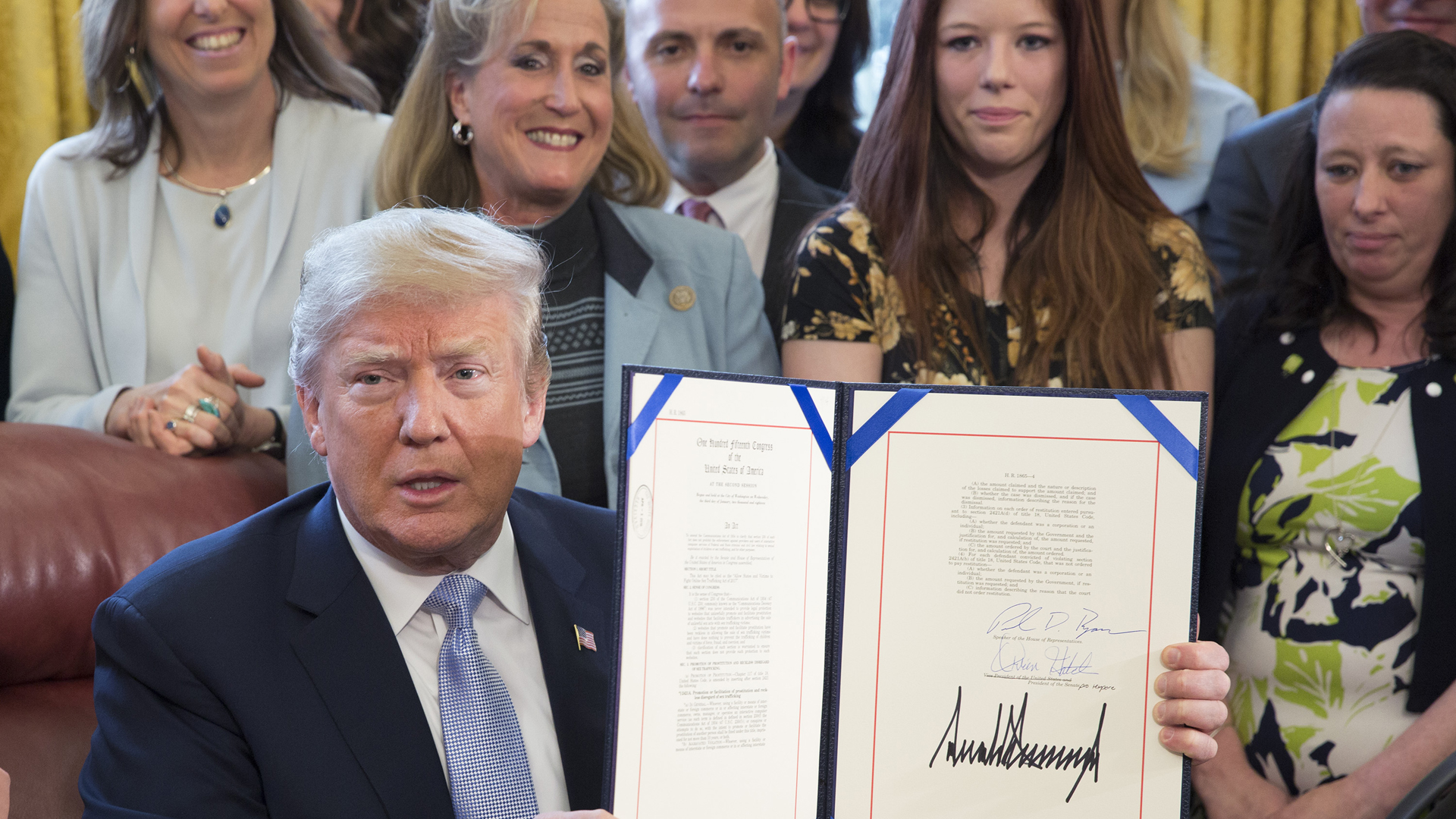 """Donald Trump displays H.R. 1865, the """"Allow States and Victims to Fight Online Sex Trafficking Act of 2017"""" after signing it into law at the White House on April 11, 2018. (Credit: Chris Kleponis-Pool/Getty Images)"""