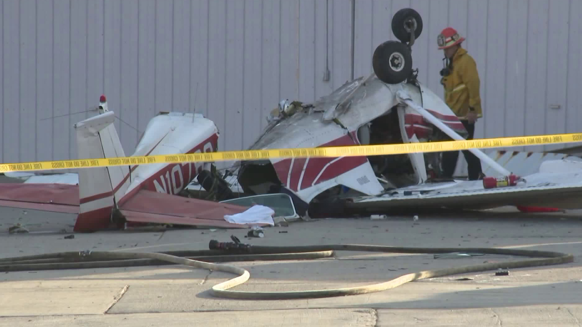 A fire official inspects the damage of a small plane crash at Whiteman Airport on Sept. 3, 2018. (Credit: KTLA)