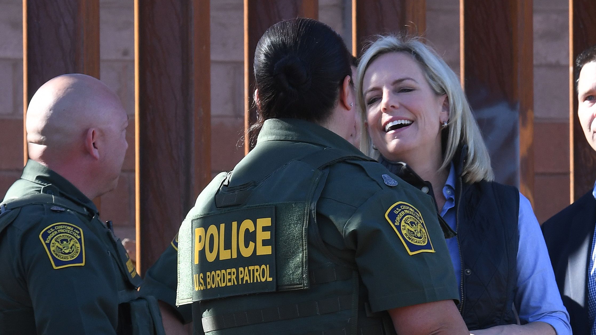 U.S. Department of Homeland Security Secretary Kirstjen M. Nielsen smiles alongside Border Patrol officer Gloria Chavez as they stand next to a plaque with President Trump's name on it at the first completed section of Trump's 30-foot border wall in the El Centro Sector, at the U.S. Mexico border in Calexico, Calif. on Oct. 26, 2018. (Credit: Mark RALSTON / AFP/ Getty Images)
