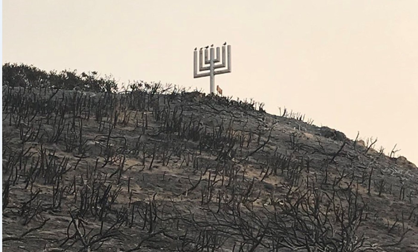 Camp Kramer's wooden Menorah and plaque honoring founder Rabbi Alfred Wolf were still standing after the camp burned in the Woolsey Fire. (Credit: Ben Poston / Los Angeles Times)