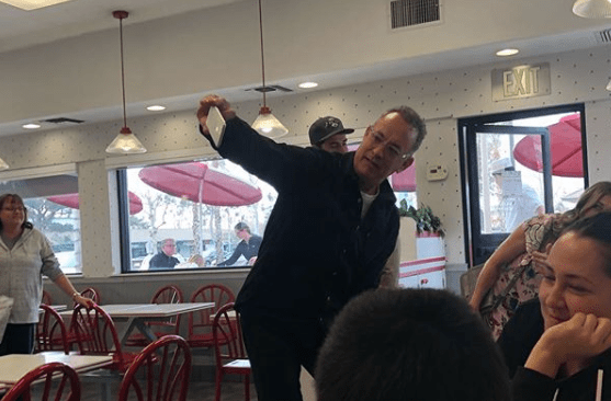 Instagram use @bookcauldron13 posted this image of Tom Hanks taking a selfie with fans on Dec. 21, 2018.