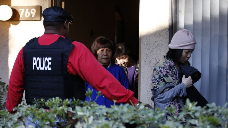 Federal agents escort residents from an apartment in Rowland Heights during a 2015 raid on an alleged birth tourism operation. (Credit: Mark Boster / Los Angeles Times)