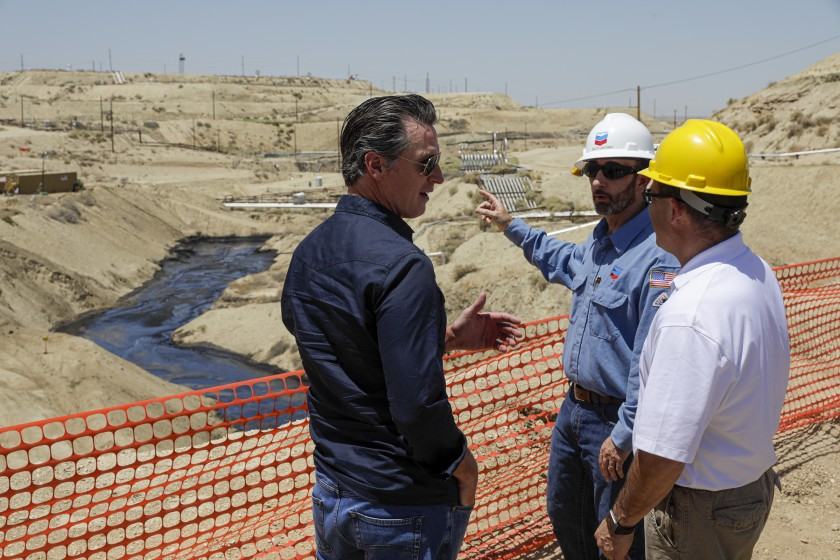 Gov. Gavin Newsom is briefed on a million-gallon spill in McKittrick by Billy Lacobie of Chevron, center, and Jason Marshall from the state Department of Conservation Division of Oil, Gas and Geothermal Resources on July 24, 2019. (Credit: Irfan Khan / Los Angeles Times )