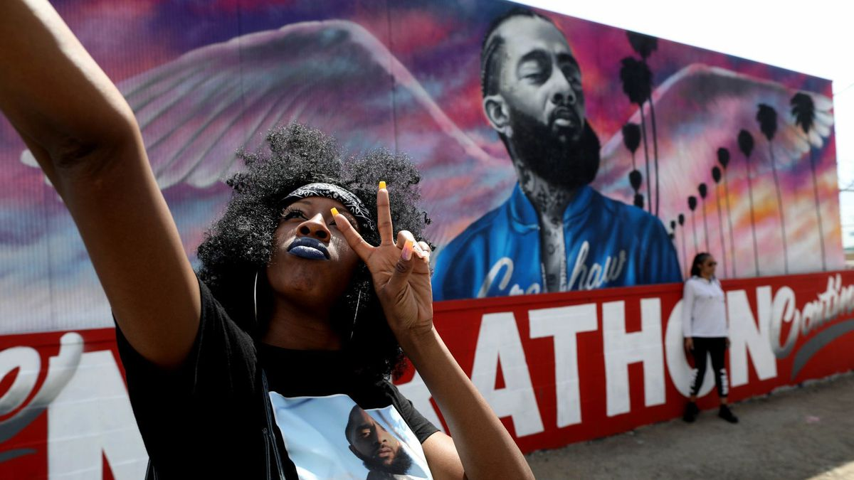 Cindy Lynn takes a photo with a mural of Nipsey Hussle near his Marathon Clothing store in an undated photo. (Credit: Gary Coronado / Los Angeles Times)