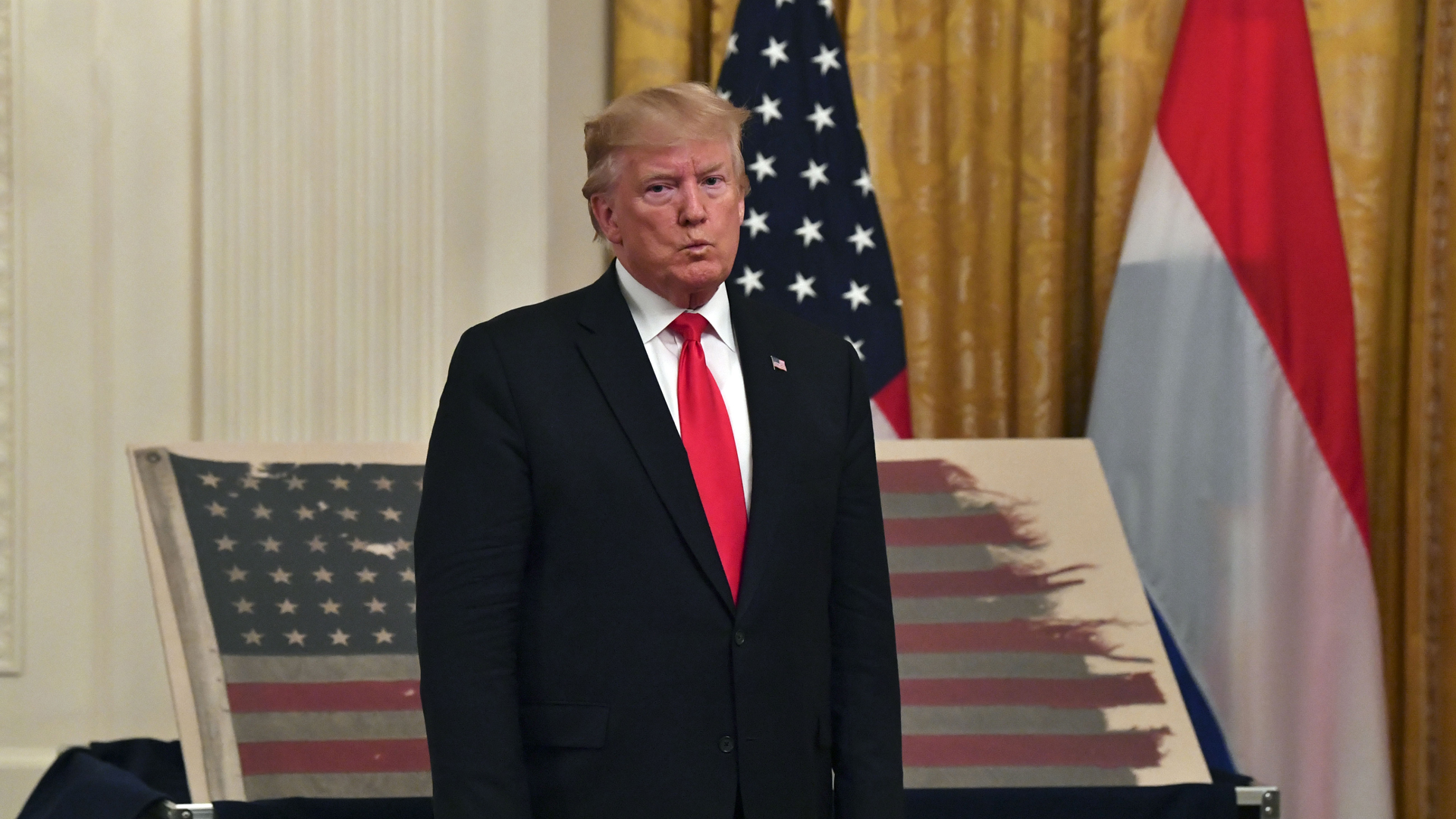 President Donald Trump stands in front of an American flag with Dutch Prime Minister Mark Rutte (not shown) during an East Room ceremony at the White House on July 18, 2019. (Credit: NICHOLAS KAMM/AFP/Getty Images)