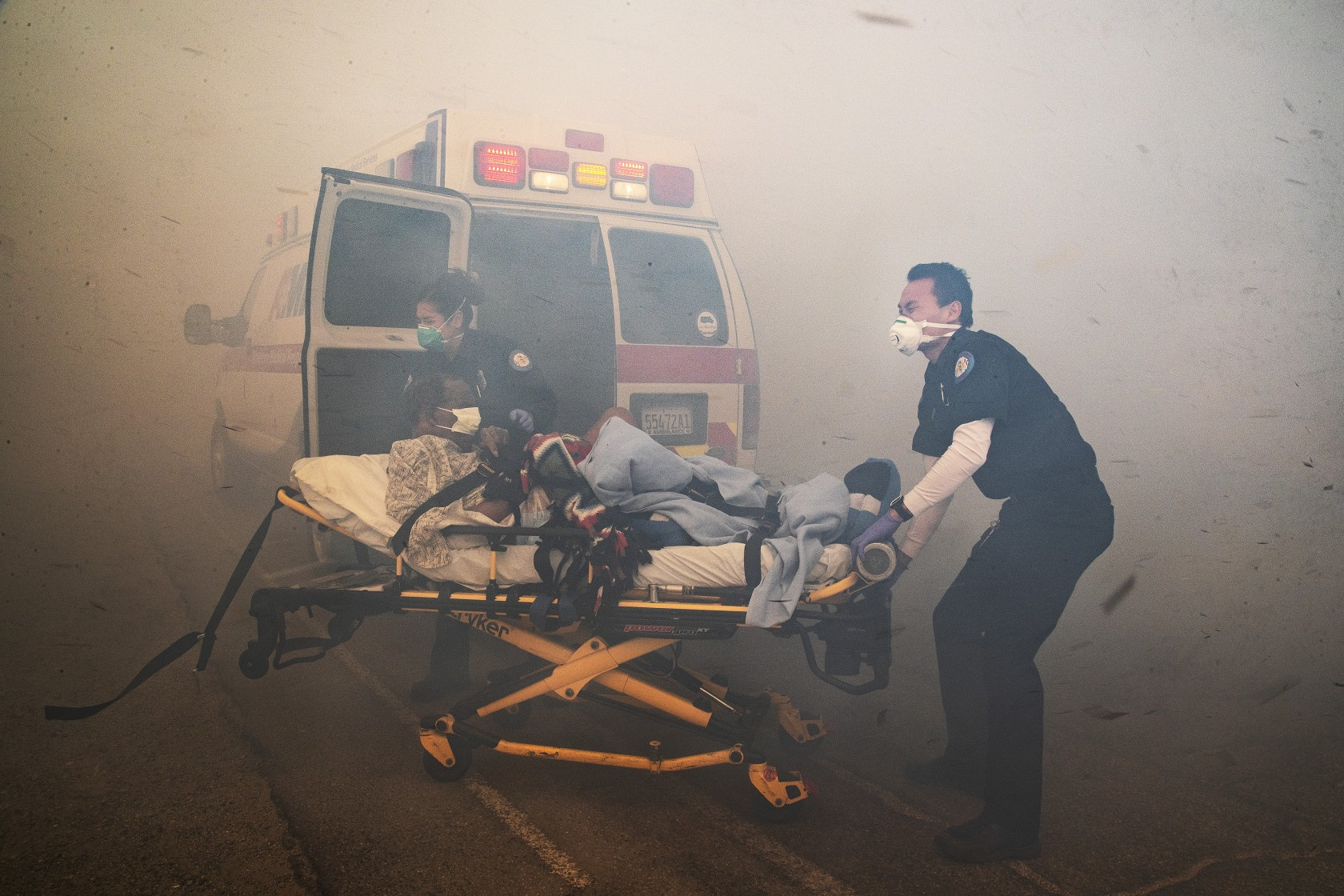 Paramedics battle thick smoke to evacuate a resident from the Riverside Heights Healthcare Center on Oct. 30 as the hill Fire burned dangerously close to the facility in Jurupa Valley. (Credit: Gina Ferazzi/ Los Angeles Times)