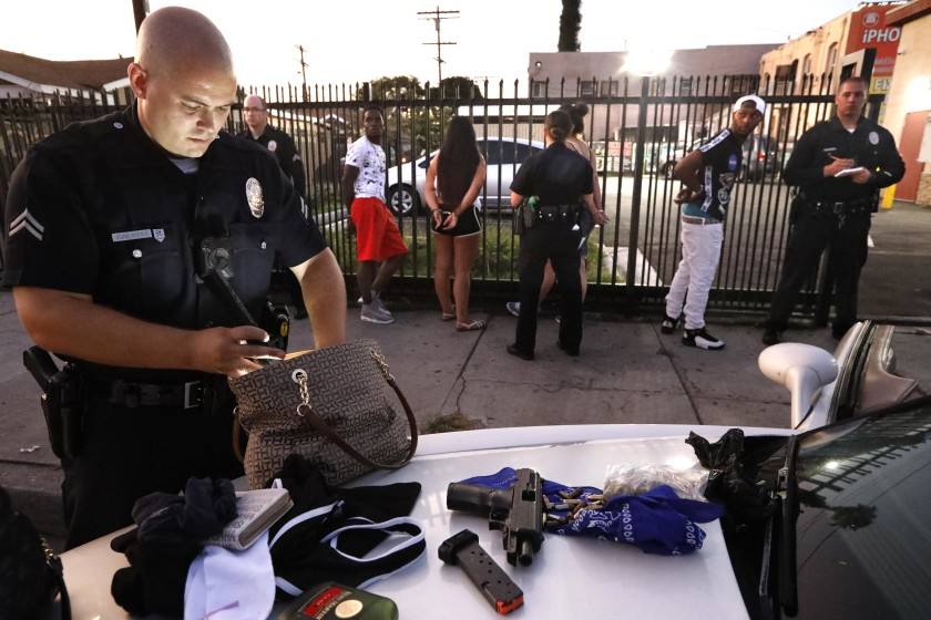 LAPD Officer Charles Kumlander searches a woman's purse after spotting a gun on the floor of a car he and his partner had pulled over in South Los Angeles in this undated photo.(Credit: Genaro Molina / Los Angeles Times)