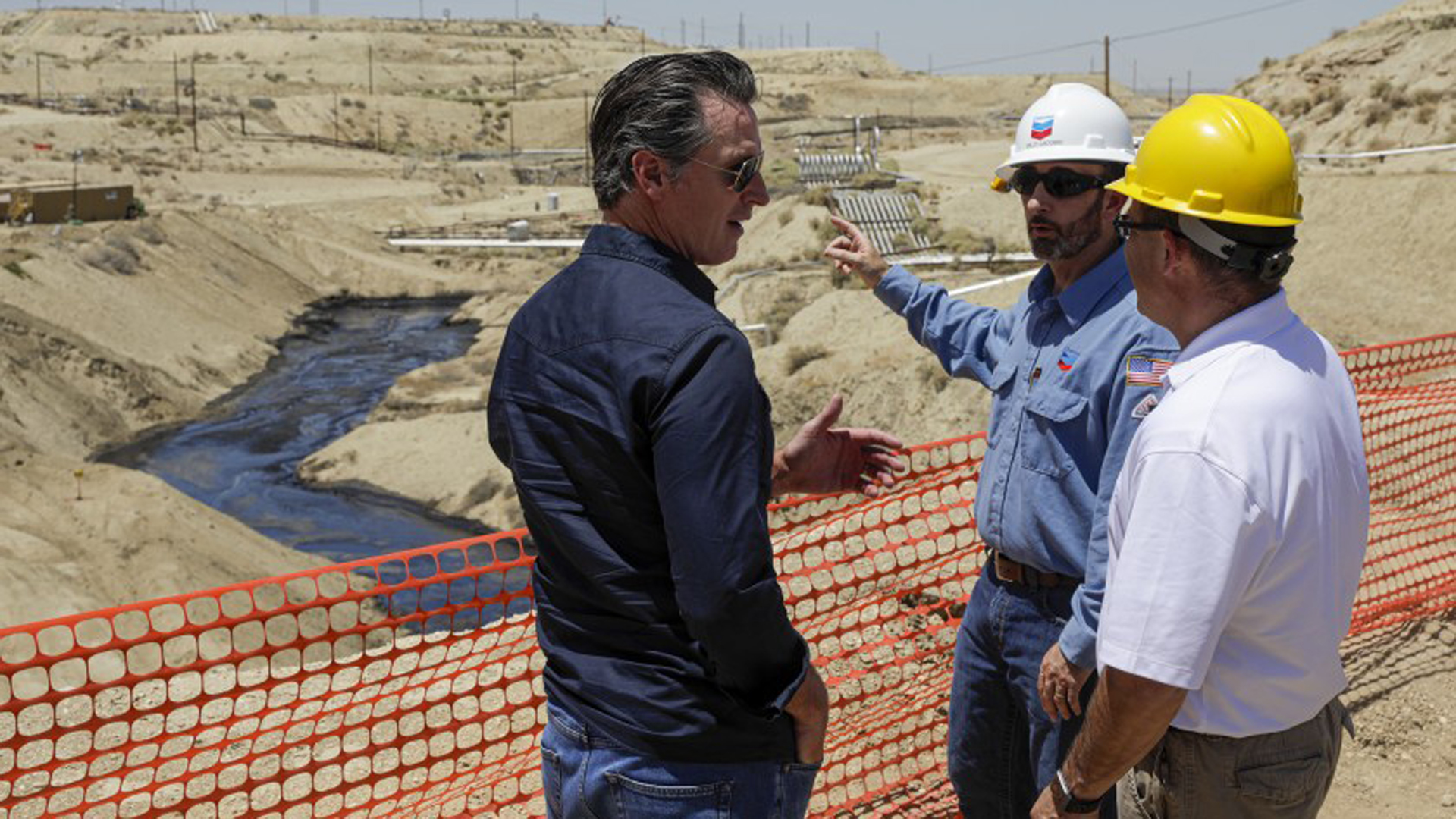 Gov. Gavin Newsom, left, is briefed by Billy Lacobie, of Chevron, center, and Jason Marshall of California department of conservation division of oil, gas, in July while touring the Chevron oil field west of Bakersfield where a spill of more than 800,000 gallons flowed into a dry creek bed. (Credit: Irfan Khan/Los Angeles Times)