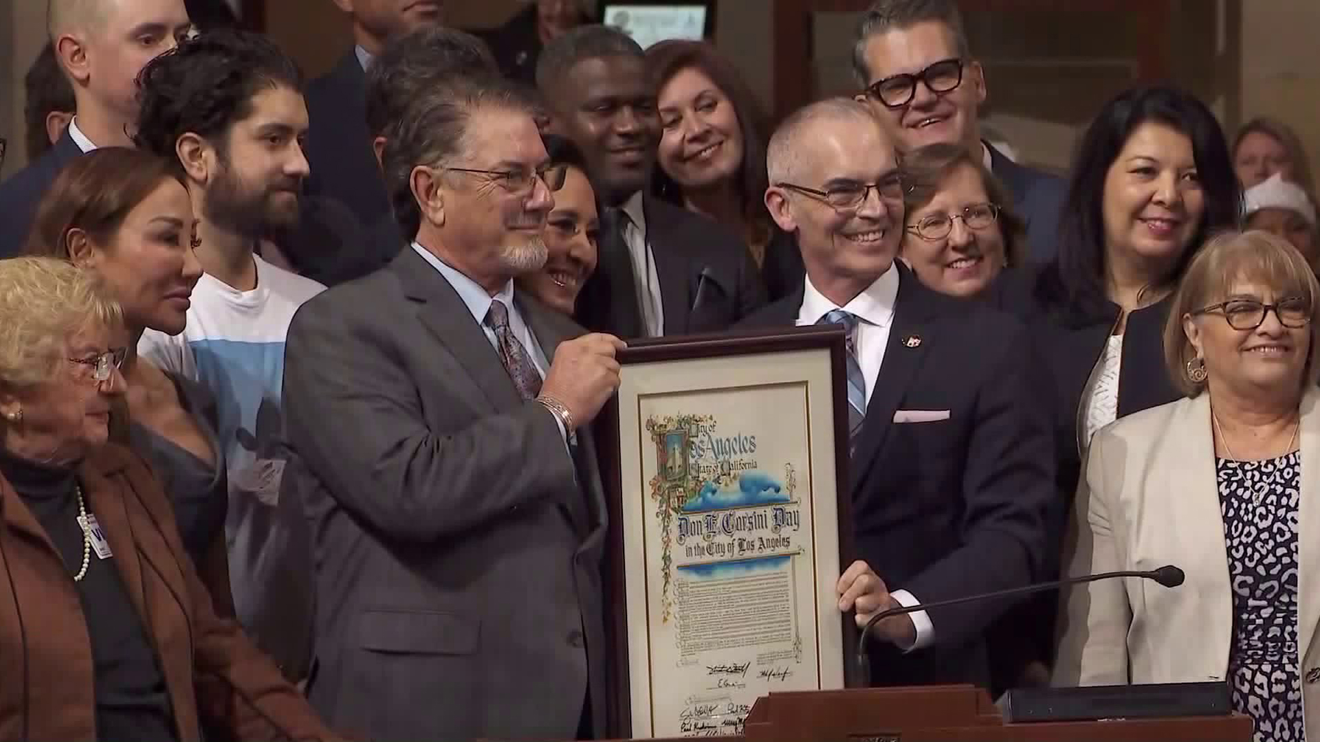 "Don Corsini, left, and Councilman Mitch O'Farrell hold a proclamation declaring Dec. 11, 2019, ""Don E. Corsini Day"" in the city of Los Angeles. (Credit: KTLA)"