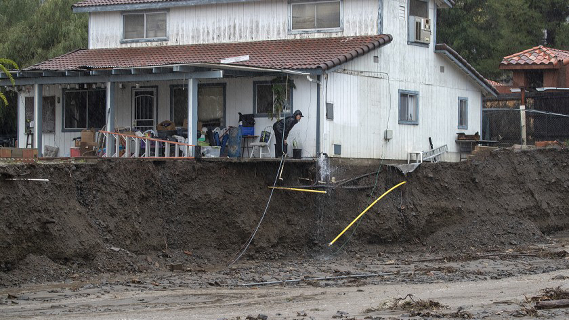 A man peers beyond the porch of his home, which was undermined by floodwater in February 2019 in Lake Elsinore's Leach Canyon.(Credit: Allen J. Schaben / Los Angeles Times)