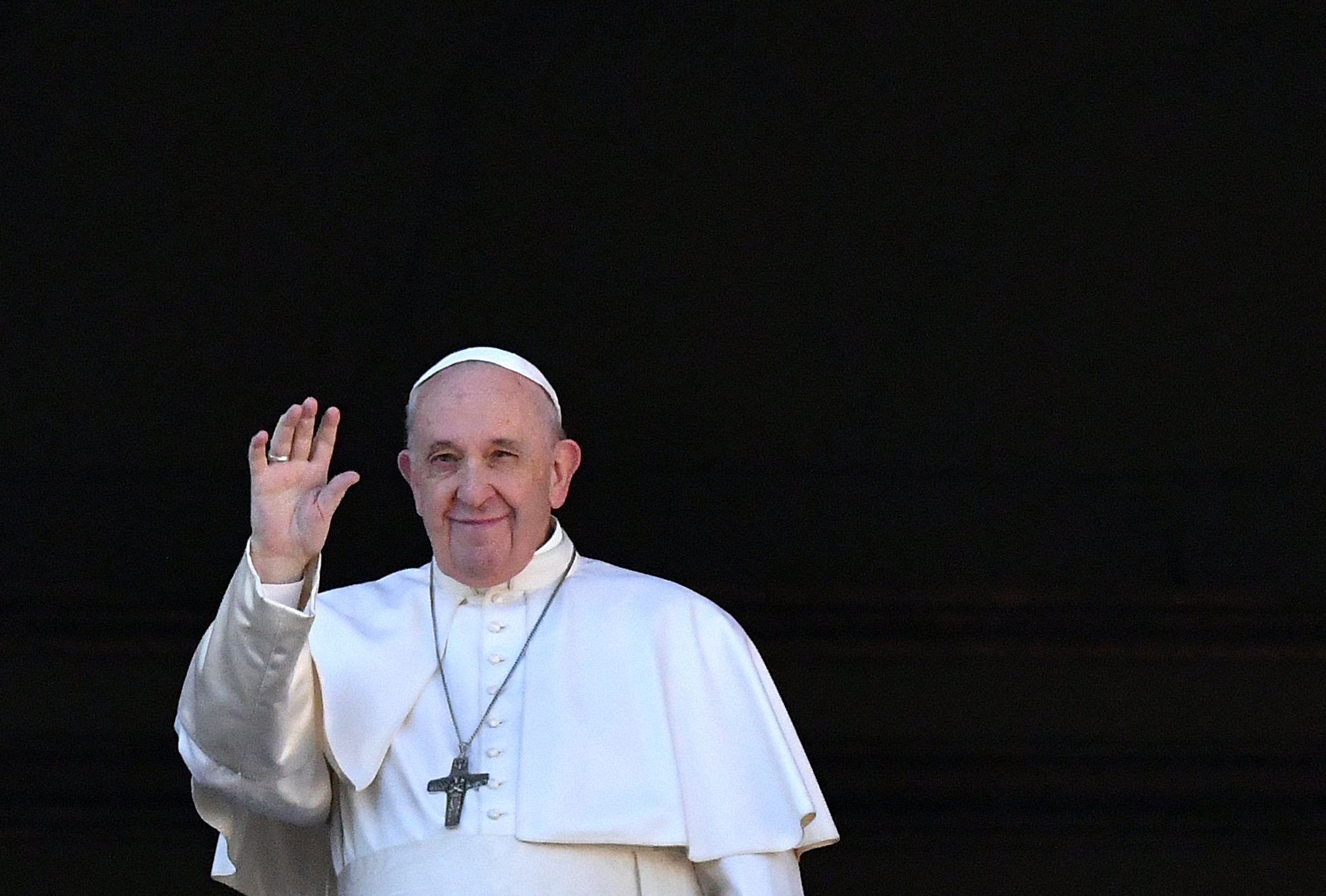"""Pope Francis waves from the balcony of St. Peter's Basilica during the traditional """"Urbi et Orbi"""" Christmas message to the city and the world, on Dec. 25, 2019 at St Peter's Square in the Vatican. (Credit: ALBERTO PIZZOLI/AFP via Getty Images)"""