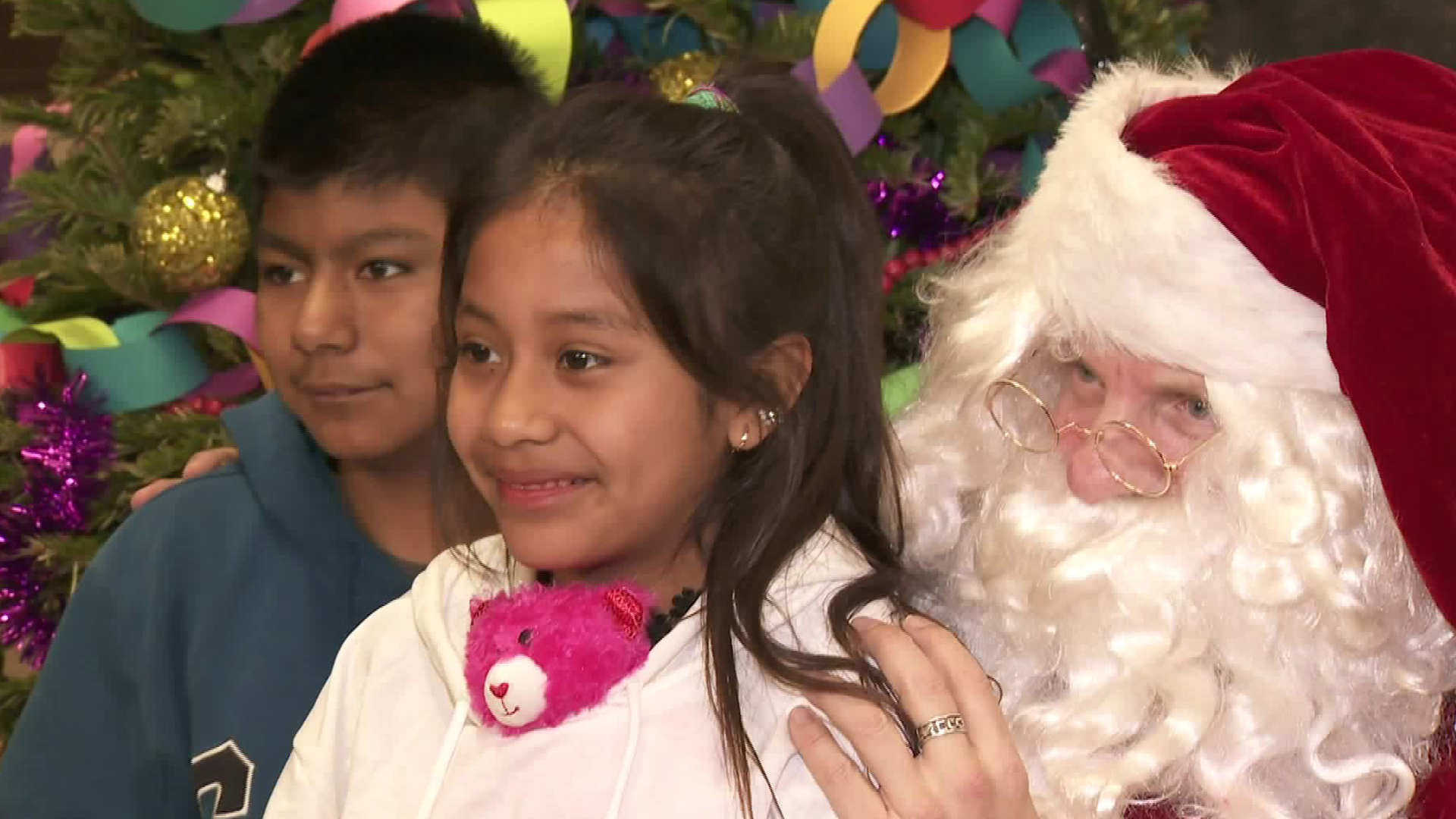 Children sit on Santa's lap during the Temple of Israel's Christmas event in Hollywood on Dec. 25, 2019. (Credit: KTLA)