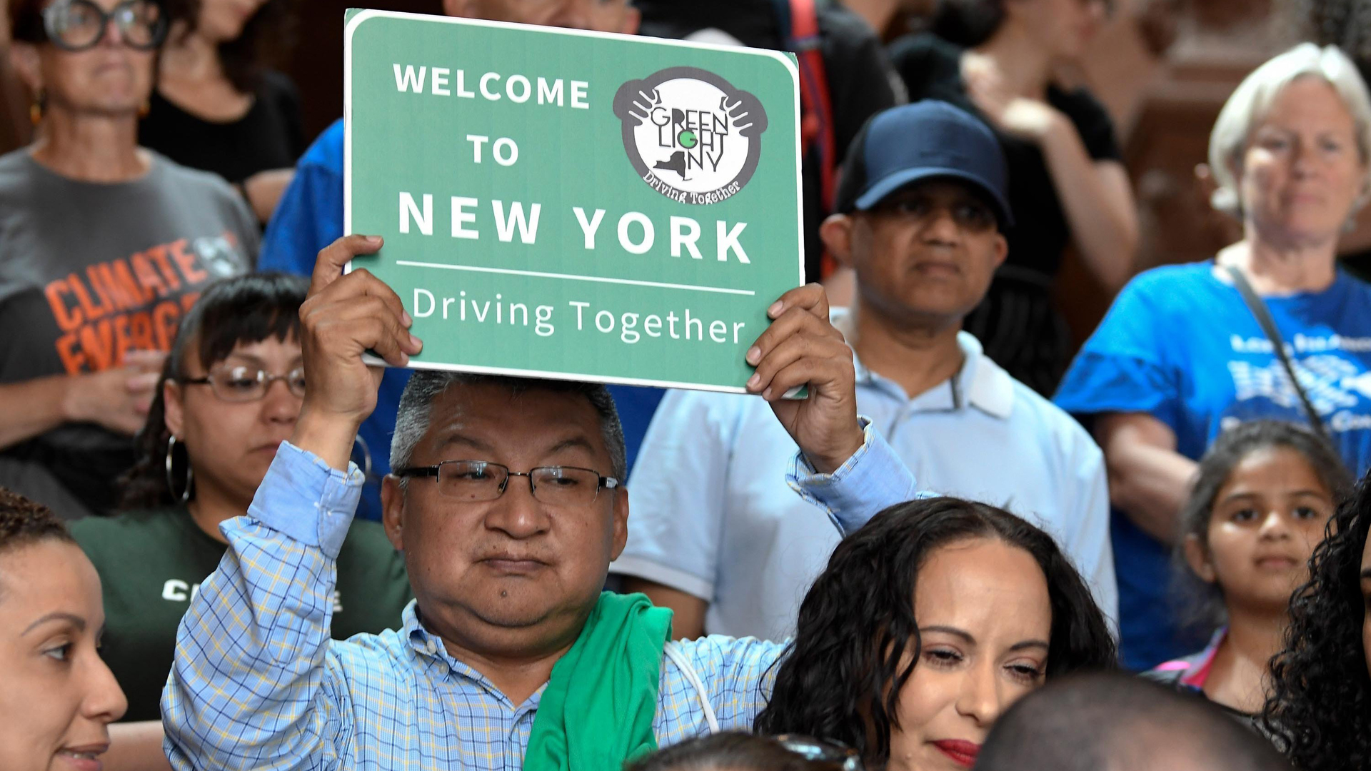 An onlooker holds up a sign as members of the New York State Assembly speak in favor of passing the Green Light Bill. (Credit: Hans Pennink/AP)
