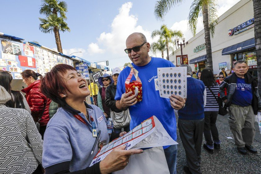 U.S. Postal Service official Rob Lindbloom promotes the Year of the Rat stamp at the Lunar New Year Festival in Monterey Park.(Credit: Irfan Khan / Los Angeles Times)