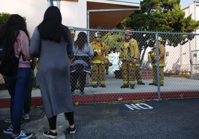 Parents wait outside Park Avenue Elementary School in Cudahy after an airplane returning to Los Angeles International Airport dropped what was believed to be engine fuel onto a school playground on Jan. 14, 2019. (Credit: Dania Maxwell/Los Angeles Times)