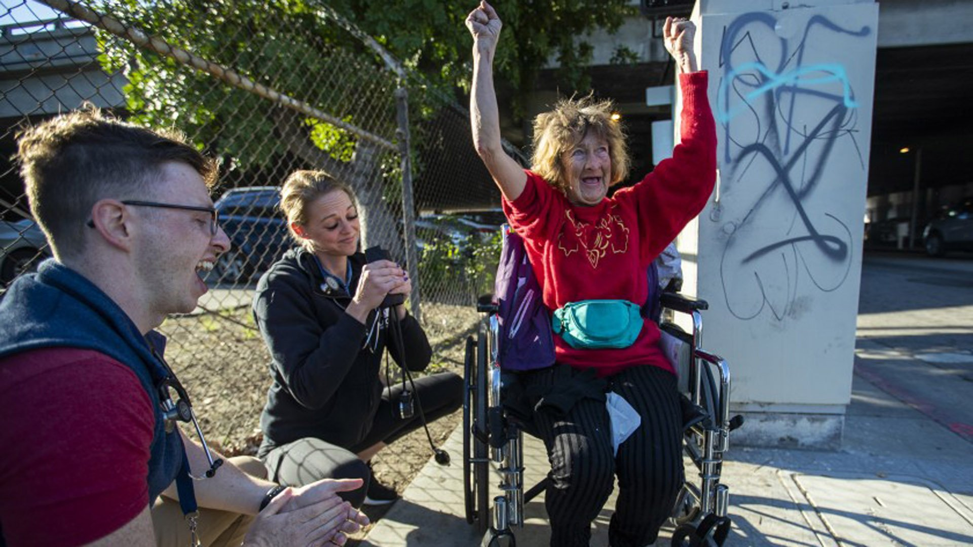 Homeless patient Dianna Hill, 61, celebrates after Dr. Michael Stefanowicz, left, and nurse Gabrielle Johnson finished monitoring her blood pressure.(Credit: Allen J. Schaben/Los Angeles Times)