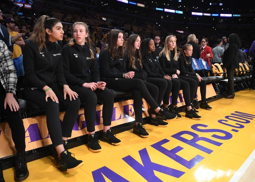 Members of Team Mamba, the girls' basketball team Kobe Bryant coached, sit courtside before a pregame ceremony at Staples Center honoring the Lakers legend and the eight others who lost their lives in a helicopter crash on Jan. 26, 2020.(Credit: Wally Skalij / Los Angeles Times)