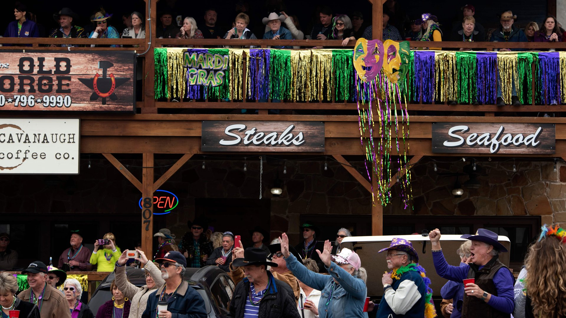 Revelers cheer as parade floats pass during the Cowboy Mardi Gras celebration in Bandera, Texas on February 15, 2020. (Credit: Mark Felix/AFP/Getty Images)