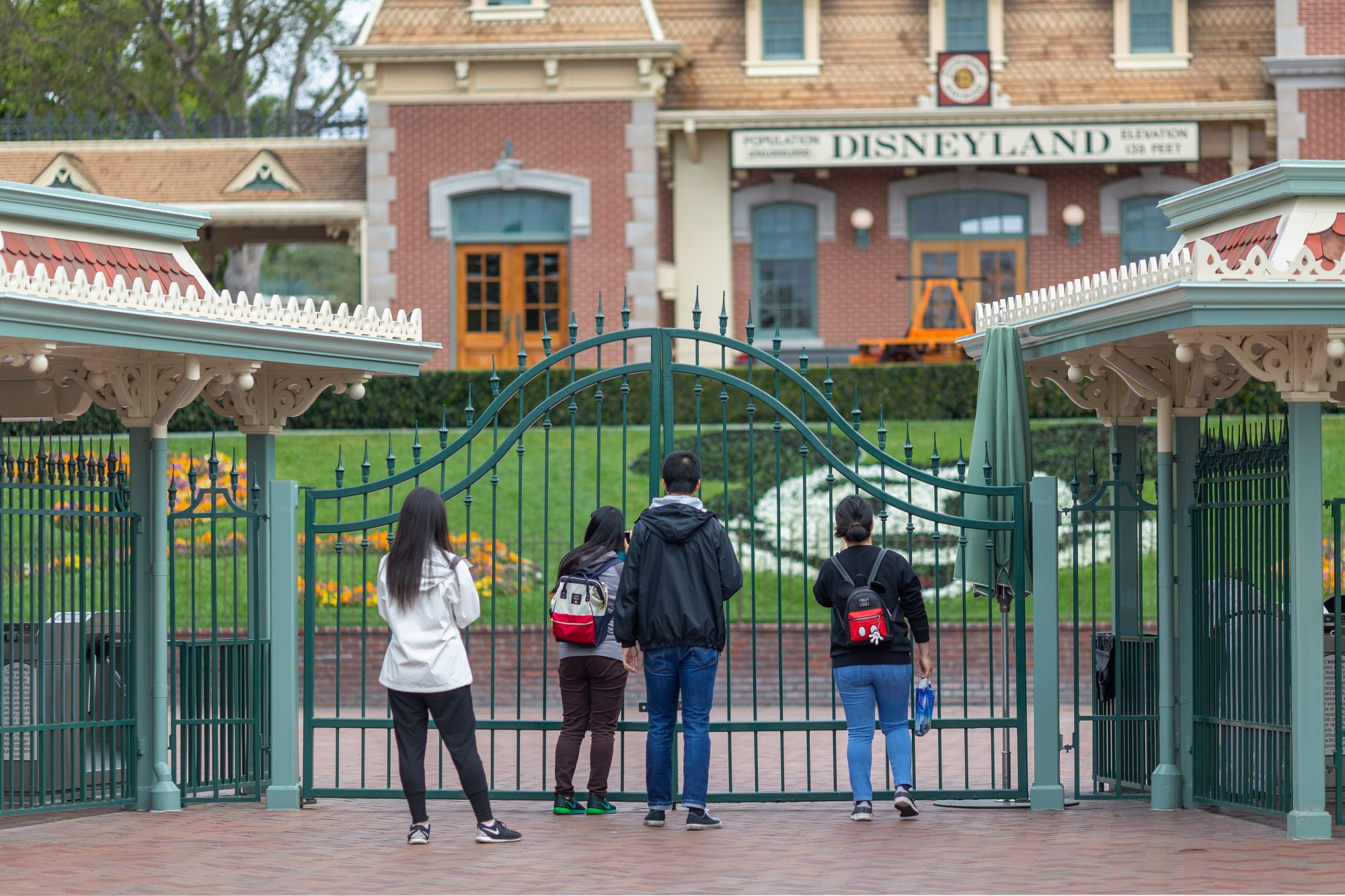 People stand outside the gates of Disneyland in Anaheim on the first day of the park's closure due to coronavirus, March 14, 2020. (Credit: David McNew / AFP / Getty Images)