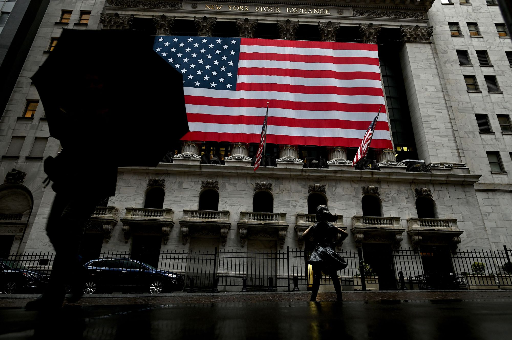 A woman walks past the New York Stock Exchange on March 19, 2020 at Wall Street in New York City. (JOHANNES EISELE/AFP via Getty Images)
