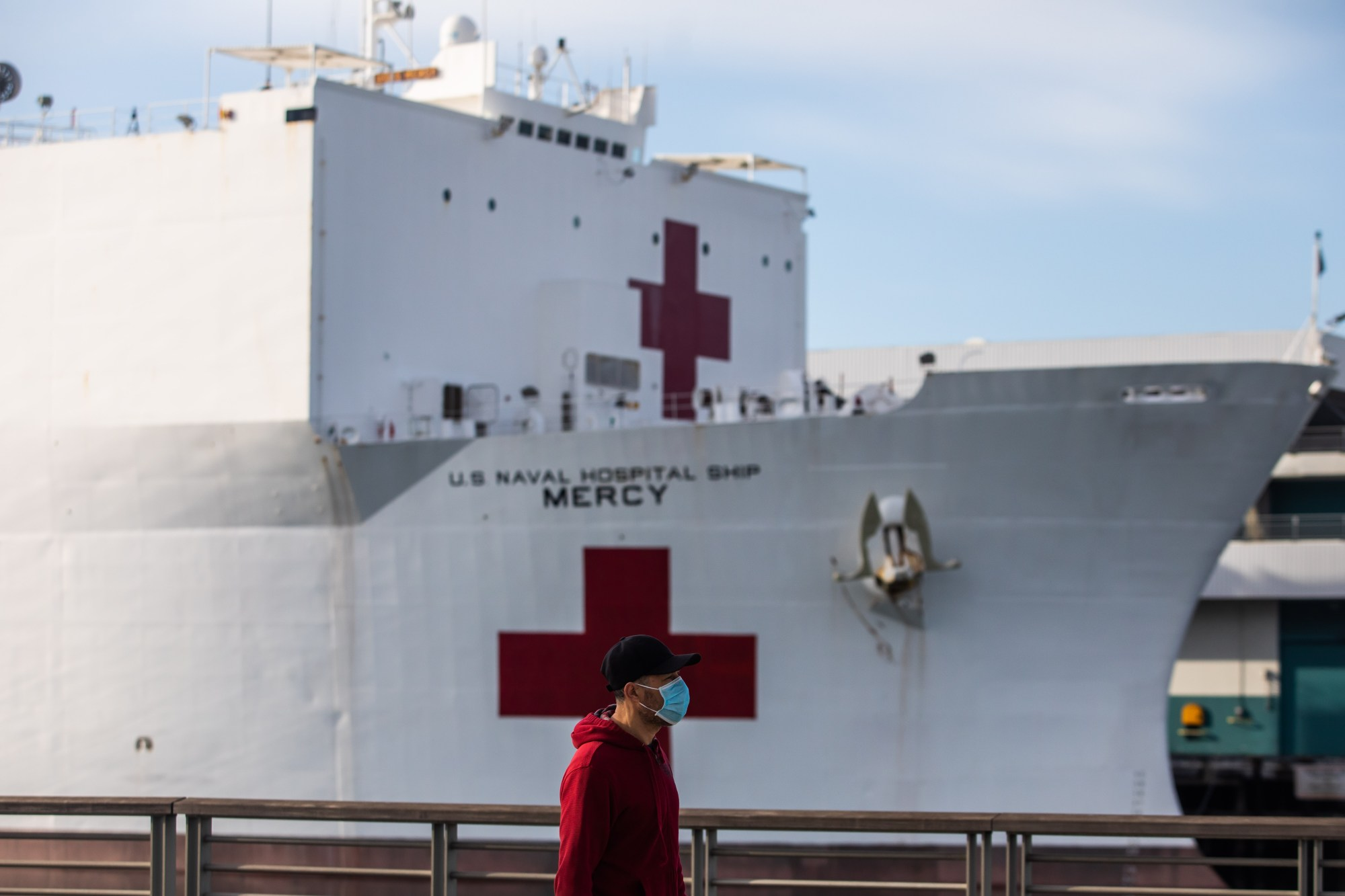 A man in a face mask walks past the U.S. Navy hospital ship, the USNS Mercy, on March 28, 2020, at the Port of Los Angeles in San Pedro. (Apu Gomes/AFP via Getty Images)