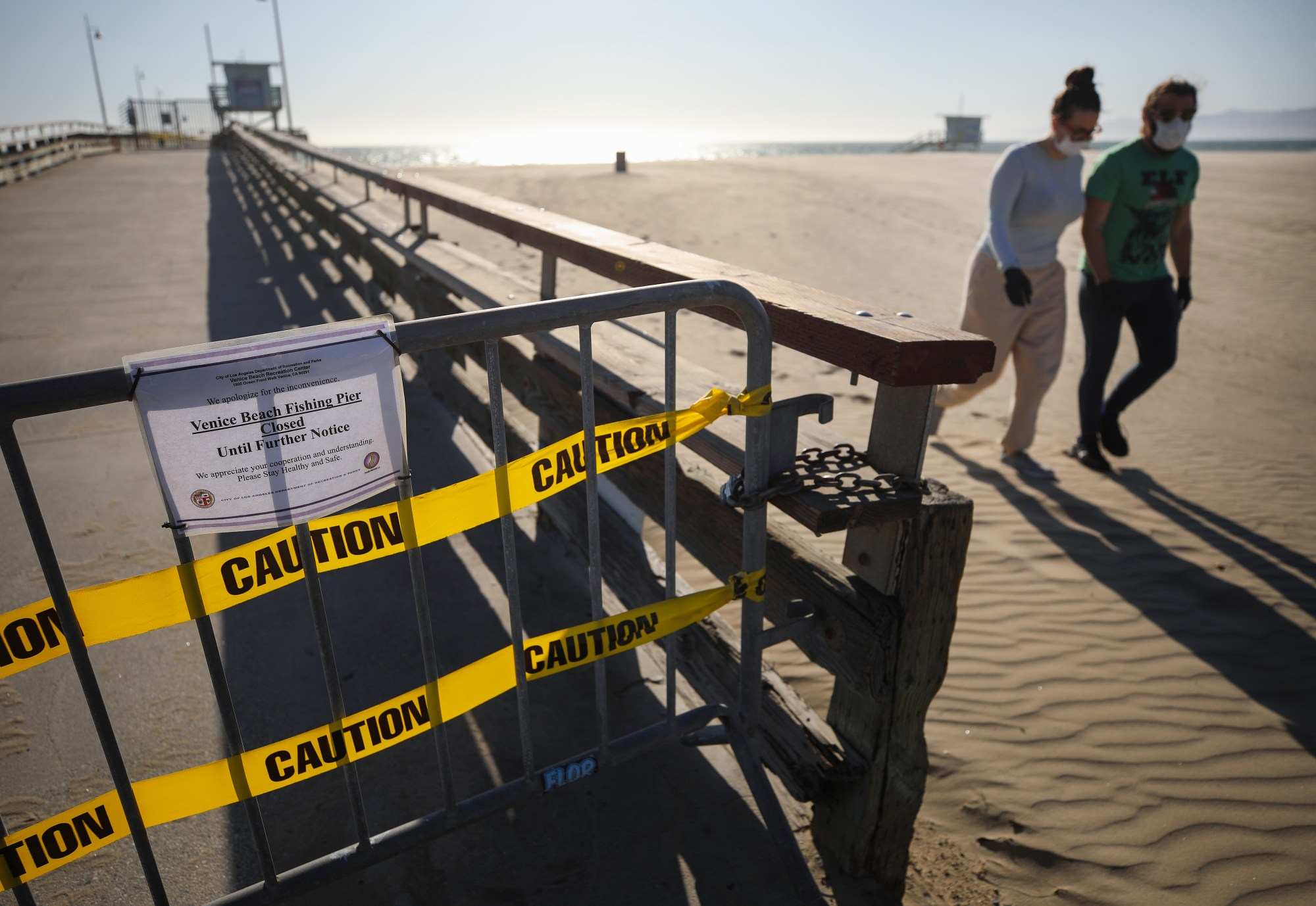 A barricade blocks the closed pier at Venice Beach as people walk past wearing face masks amid the coronavirus pandemic on March 27, 2020, in Venice, Calif. Los Angeles County closed all beaches that day as a measure to stem the spread of COVID-19. (Mario Tama/Getty Images)