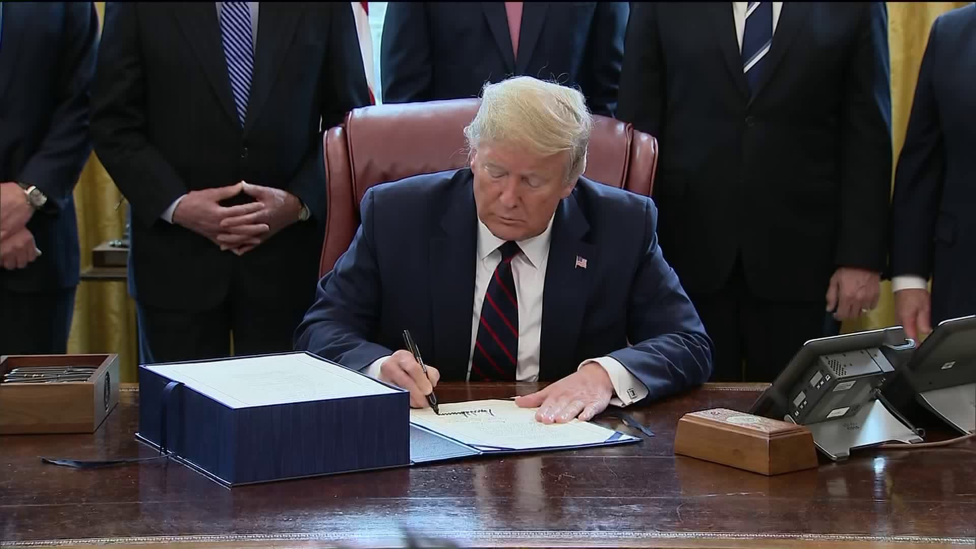 President Donald Trump signs a $2.2 trillion stimulus package to aid in COVID-19 recovery on March 27, 2020. (Credit: KTLA)