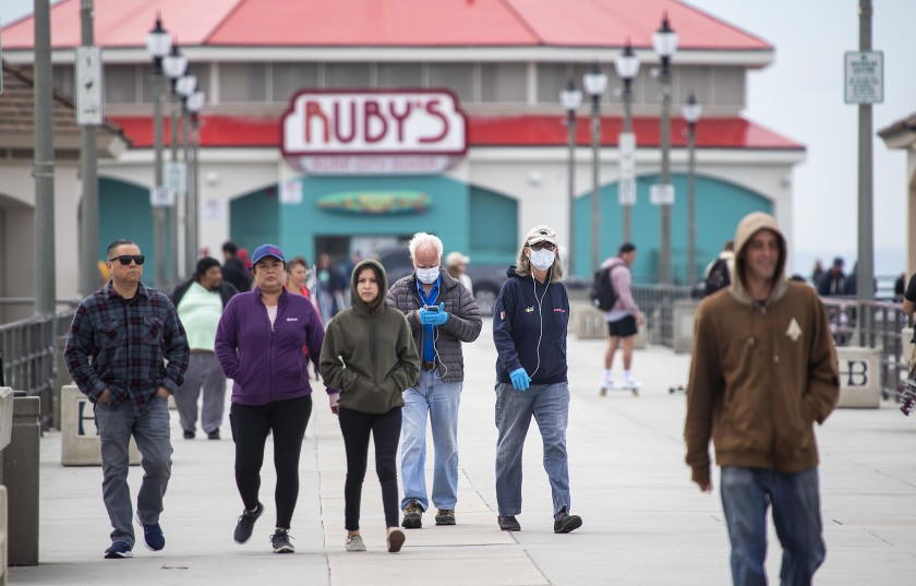 Dallas and Janet Weaver wear protective masks March 18 as they return from a walk on the Huntington Beach pier.(Allen J. Schaben / Los Angeles Times)