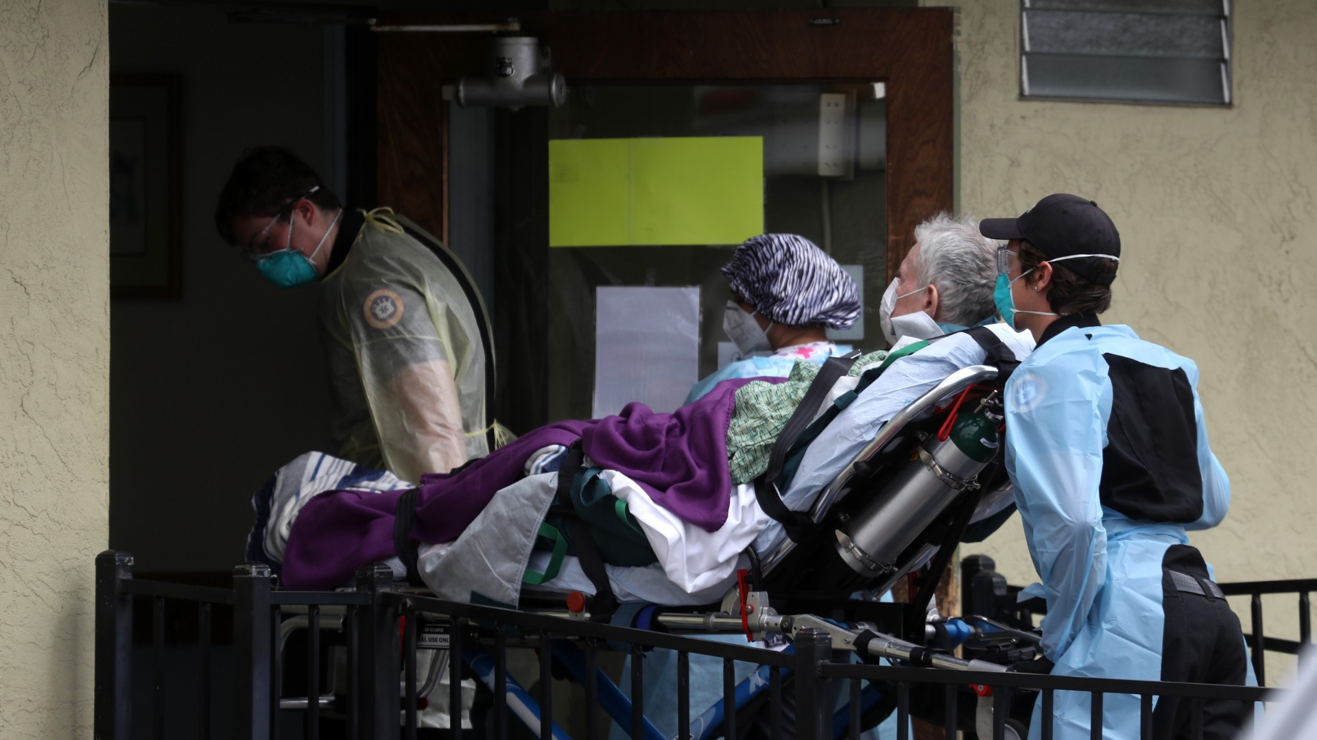 Emergency medical technicians with Royal Ambulance move a patient on a gurney from an ambulance into the Gateway Care and Rehabilitation Center on April 16, 2020 in Hayward, California. (Justin Sullivan/Getty Images)