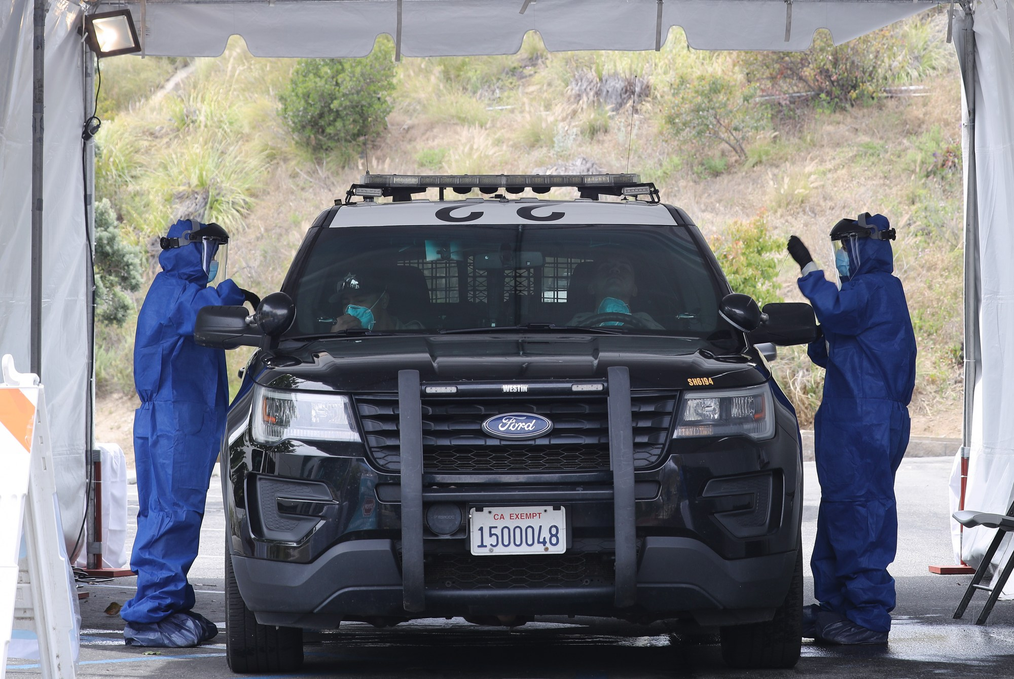 Volunteers in personal protective equipment conduct drive-through coronavirus testing with police officers at Malibu City Hall on April 8, 2020. (Mario Tama/Getty Images)
