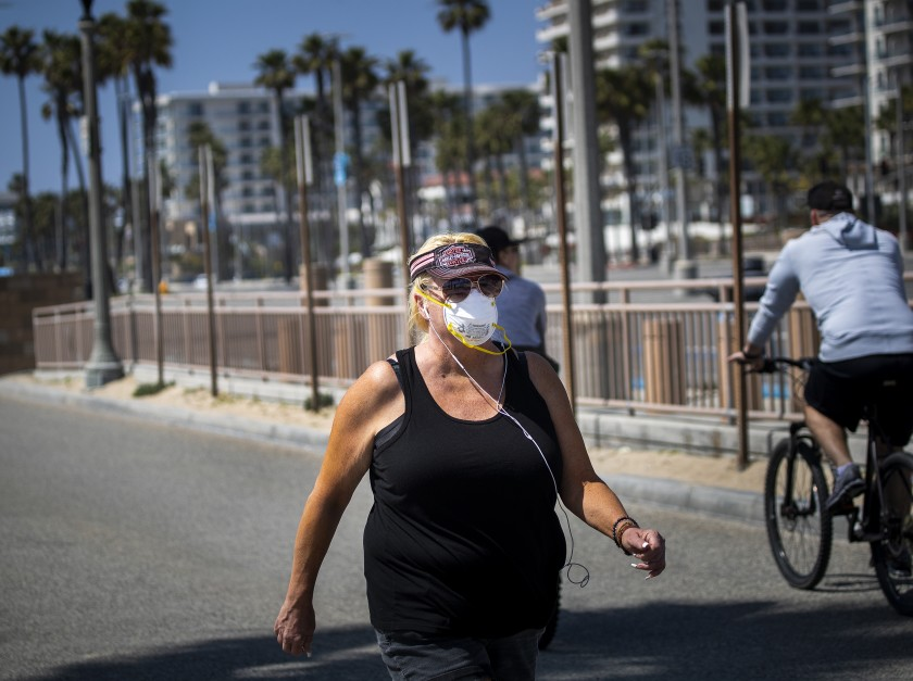 A woman wears a protective mask while exercising on the boardwalk in Huntington Beach on April 2, 2020. (Credit: Allen J. Schaben / Los Angeles Times)