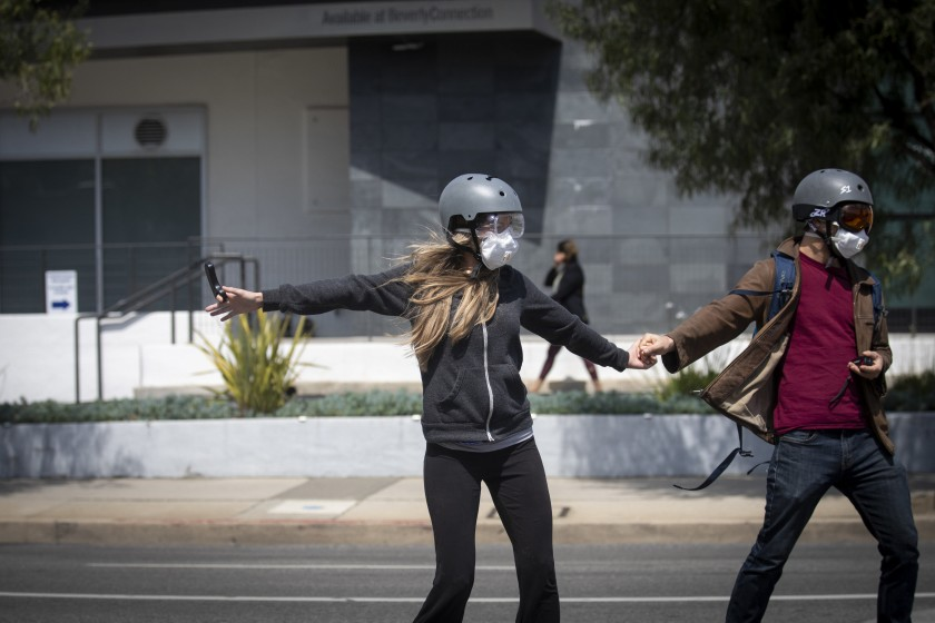 A couple wear masks, helmets and eye protection while skateboarding in Beverly Hills in March 2020. (Credit: Francine Orr / Los Angeles Times)