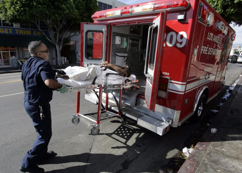 A Los Angeles Fire Department paramedic is seen with a patient in this undated photo. (Los Angeles Times)