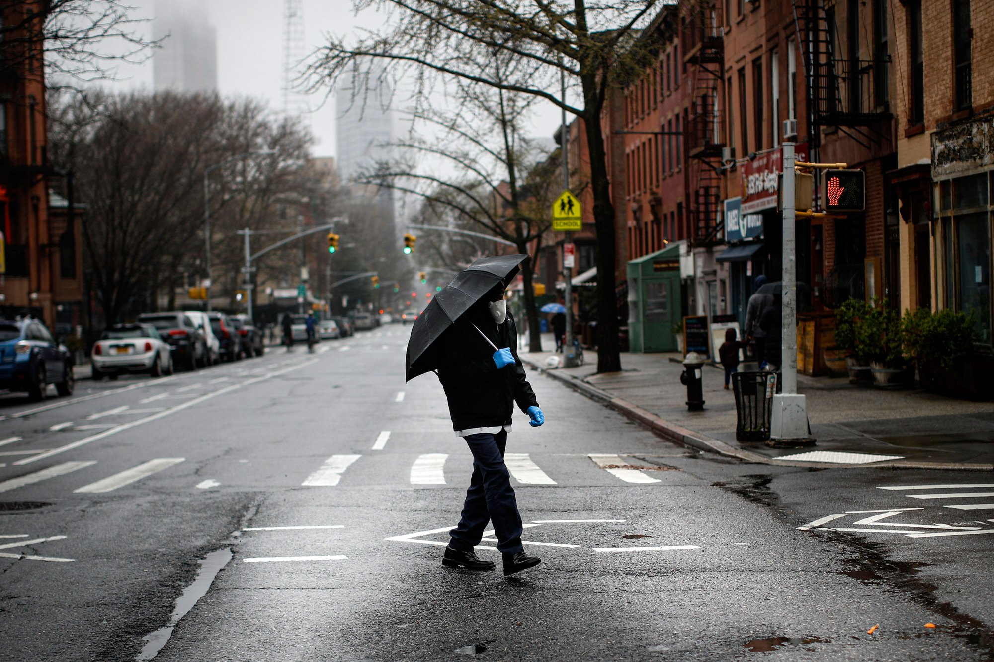 A pedestrian wearing a protective mask and protective gloves walks across an empty Dekalb Avenue, Sunday, March 29, 2020, in Brooklyn borough of New York. The new coronavirus causes mild or moderate symptoms for most people, but for some, especially older adults and people with existing health problems, it can cause more severe illness or death. (AP Photo/John Minchillo)