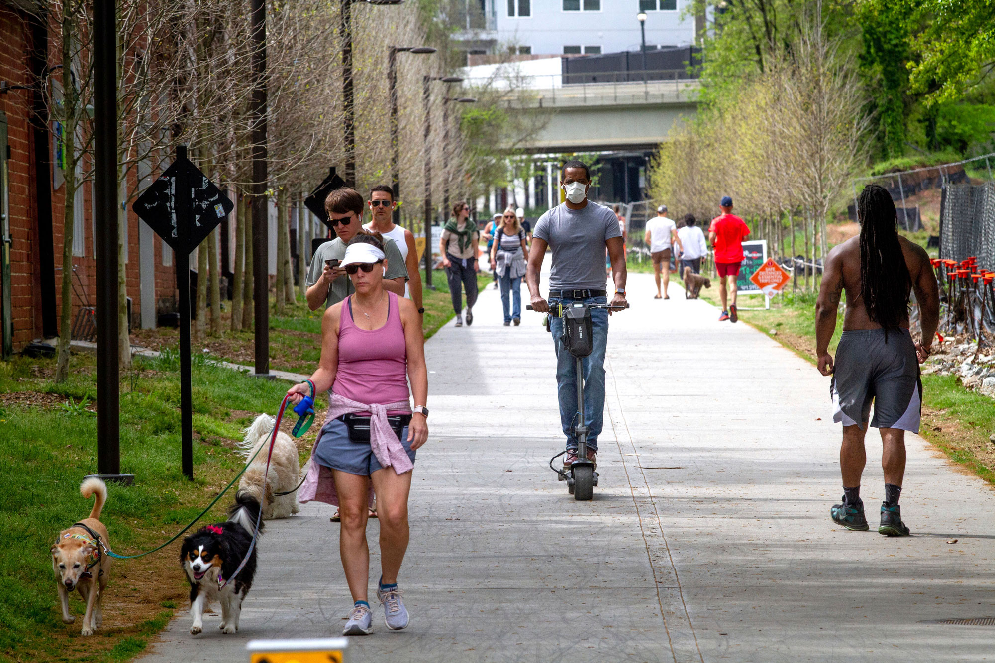 Marcus Bouliany, center, wears a mask while making his way along the BeltLine in Atlanta, during the coronavirus outbreak Saturday, April 4, 2020. (Steve Schaefer/AP