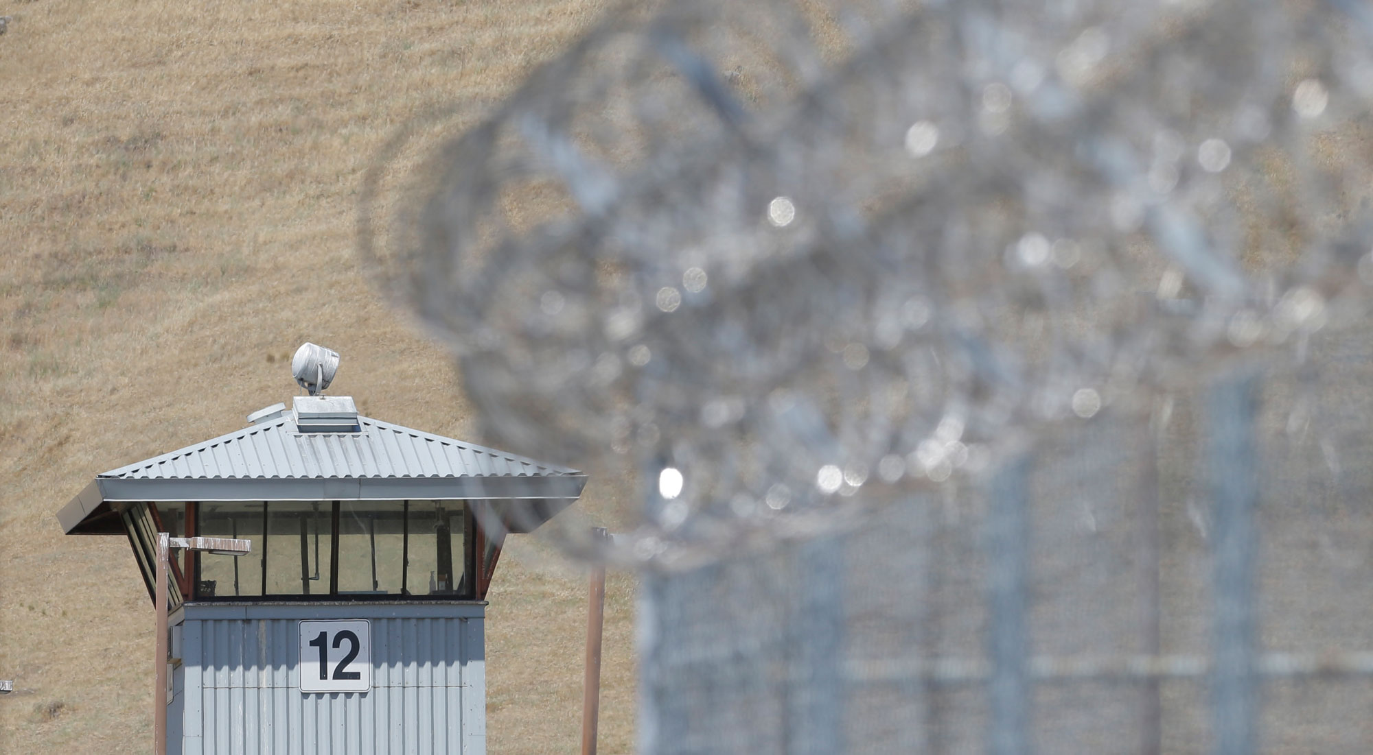In this photo taken Wednesday May 20, 2015, a guard tower and razor wire are seen at California State Prison, Solano in Vacaville, Calif. Authorities are investigating the murder of Nicholas Anthony Rodriguez a the prison in May. An autopsy report reveals that Rodriguez' body was cut apart and most of his major body organs removed, prompting an investigation of whether a riot by dozens of prisoners was used to cover up the homicide.(AP Photo/Rich Pedroncelli)