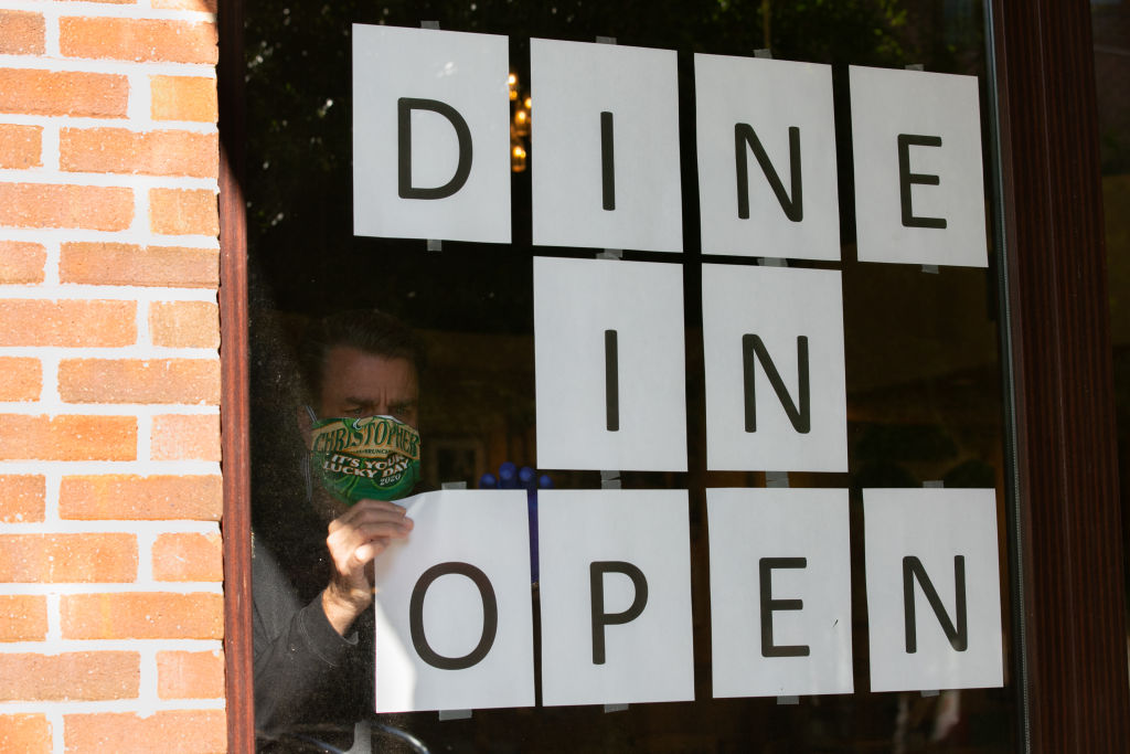 Barry Lennon, Operating Partner of J. Christopher, hangs up signs to to promote dine in service now available in the J. Christopher restaurant on April 27, 2020 in Brookhaven, Georgia. (Jessica McGowan/Getty Images)