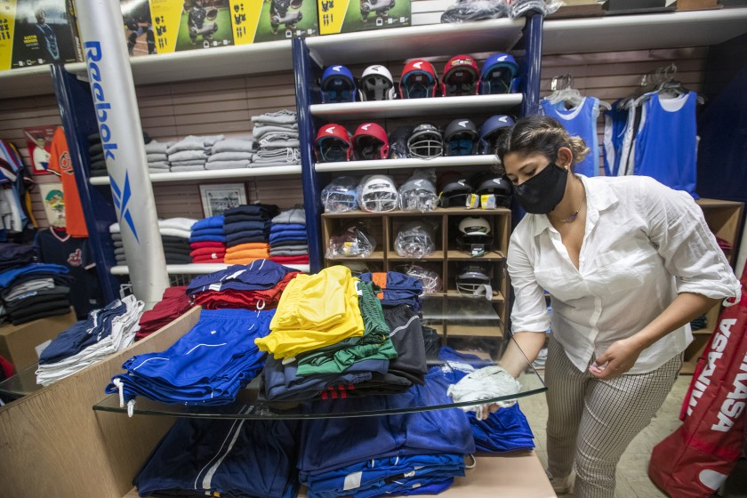 Daniela Prieto, an employee at Deportes Prieto in Boyle Heights, disinfects inside the store, which is currently allowing customers to preorder merchandise. The business reopened Monday for curbside pickup only.(Mel Melcon / Los Angeles Times)