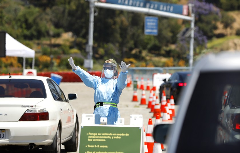 A person directs traffic at a drive-through coronavirus testing site at Dodger Stadium. (Christina House / Los Angeles Times)