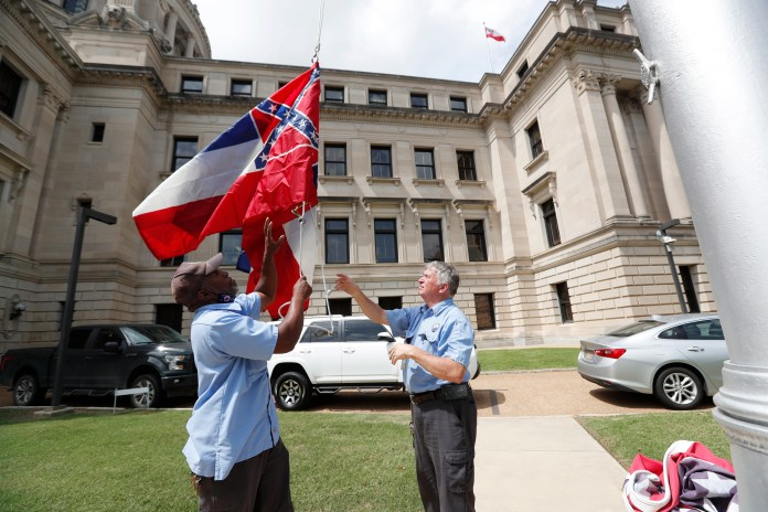 Mississippi Department of Finance and Administration employees Willie Townsend, left, and Joe Brown, raise a couple of Mississippi state flags over the Capitol grounds in Jackson on June 30, 2020. (Rogelio V. Solis/Associated Press)