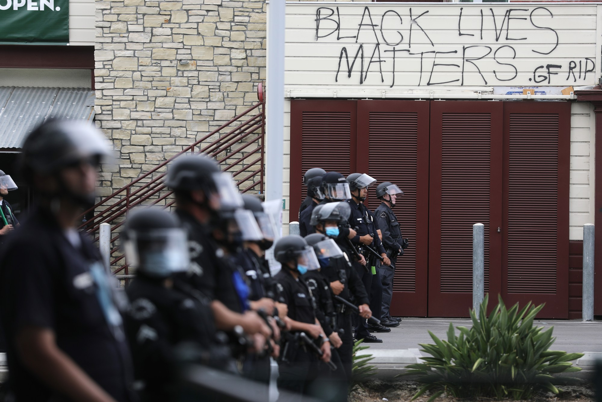 LAPD officers keep watch beneath graffiti reading 'Black Lives Matters' during demonstrations following the death of George Floyd on May 30, 2020. (Mario Tama/Getty Images)