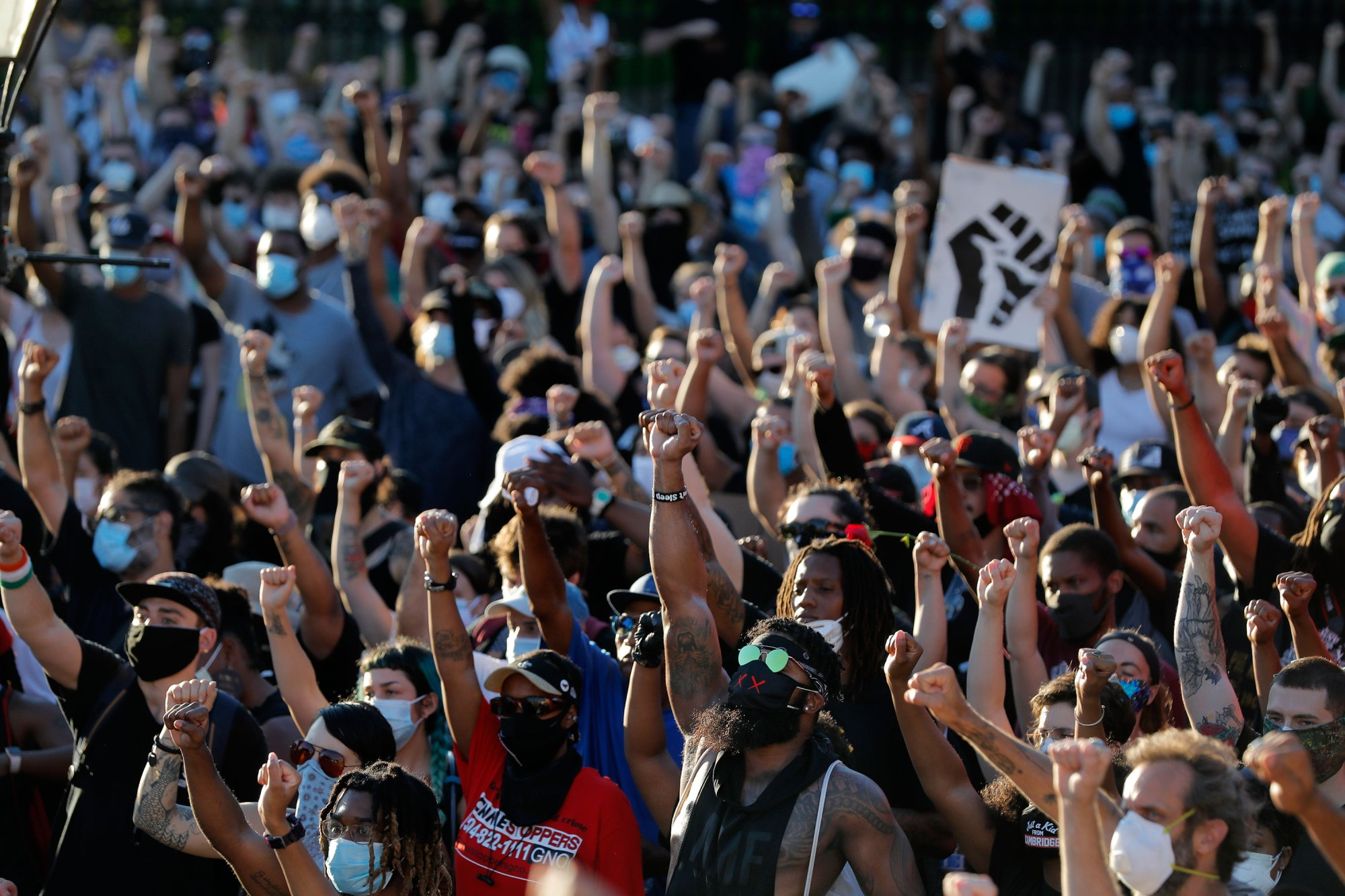 People raise their fists during a rally outside Jackson Square in New Orleans on Friday. George Floyd's second memorial will take place Saturday in Hoke County, North Carolina. (Gerald Herbert/AP via CNN Wire)