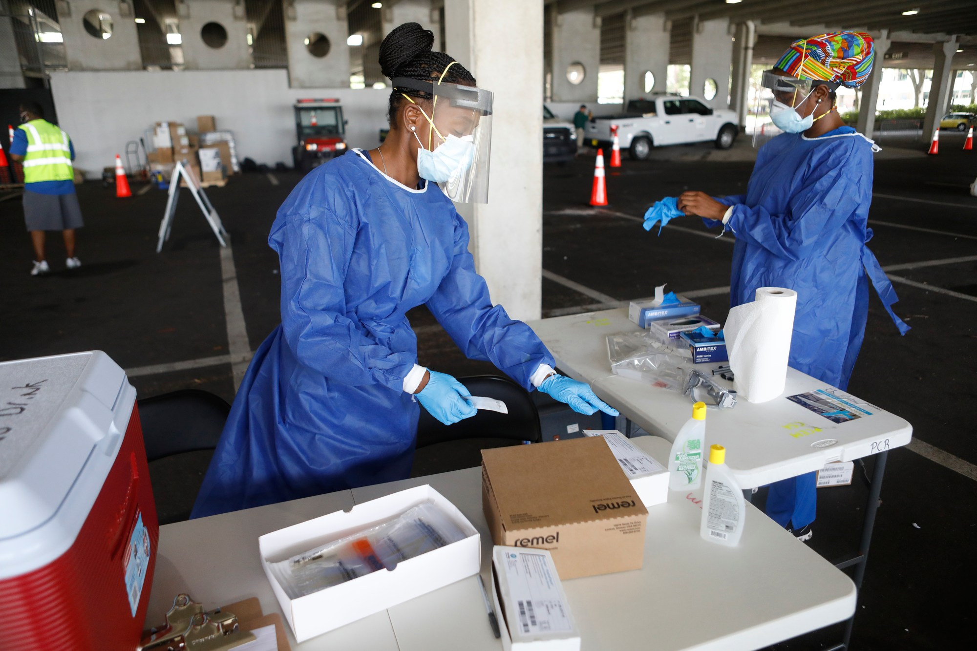 Registered nurses Gina Aubourg and Renee Lewis begin testing at the COVID-19 drive-thru site at the Duke Energy for the Arts Mahaffey Theater on July 8, 2020 in St. Petersburg, Florida. (Octavio Jones/Getty Images)