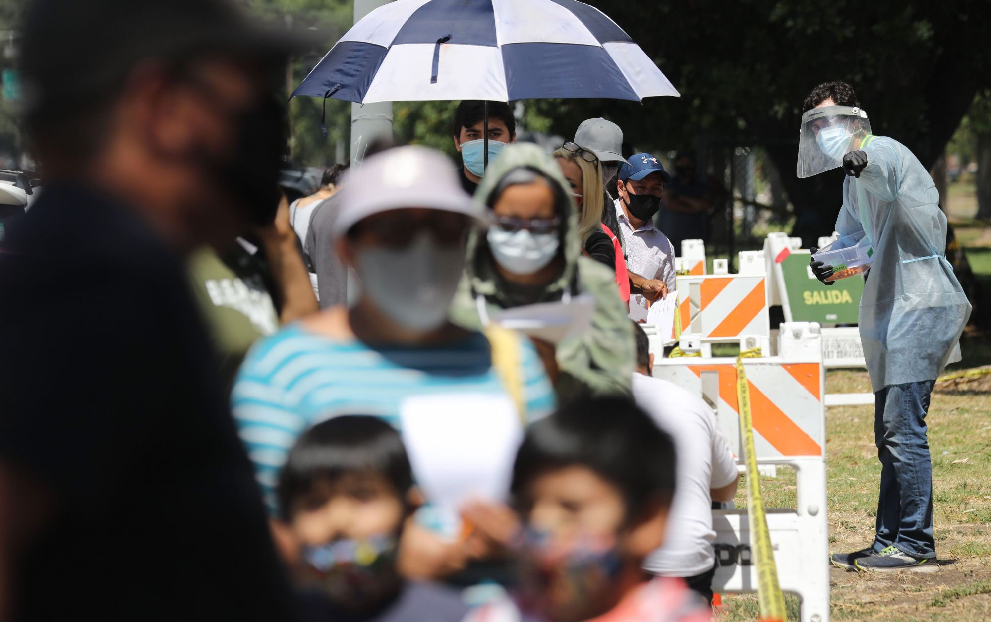 A COVID-19 testing associate dressed in personal protective equipment (PPE) assists people waiting in line at a testing center at Lincoln Park amid the coronavirus pandemic on July 07, 2020 in Los Angeles, California. (Mario Tama/Getty Images)