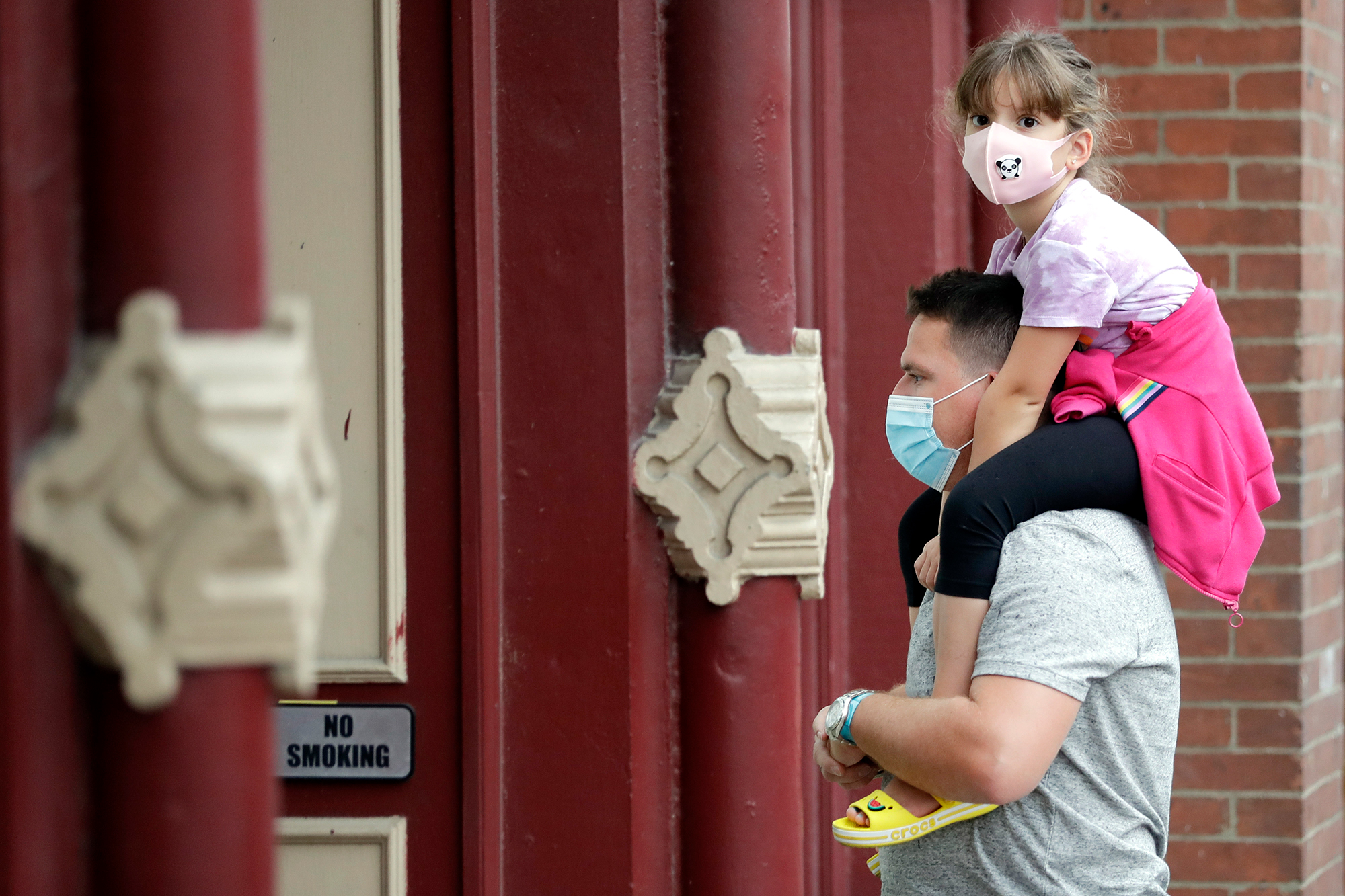 A man and a girl hear a band outside a music venue in Nashville, Tenn. The Nashville Health Department has a mask mandate to help battle the spread of the coronavirus. (Mark Humphrey/AP via CNN Wire)