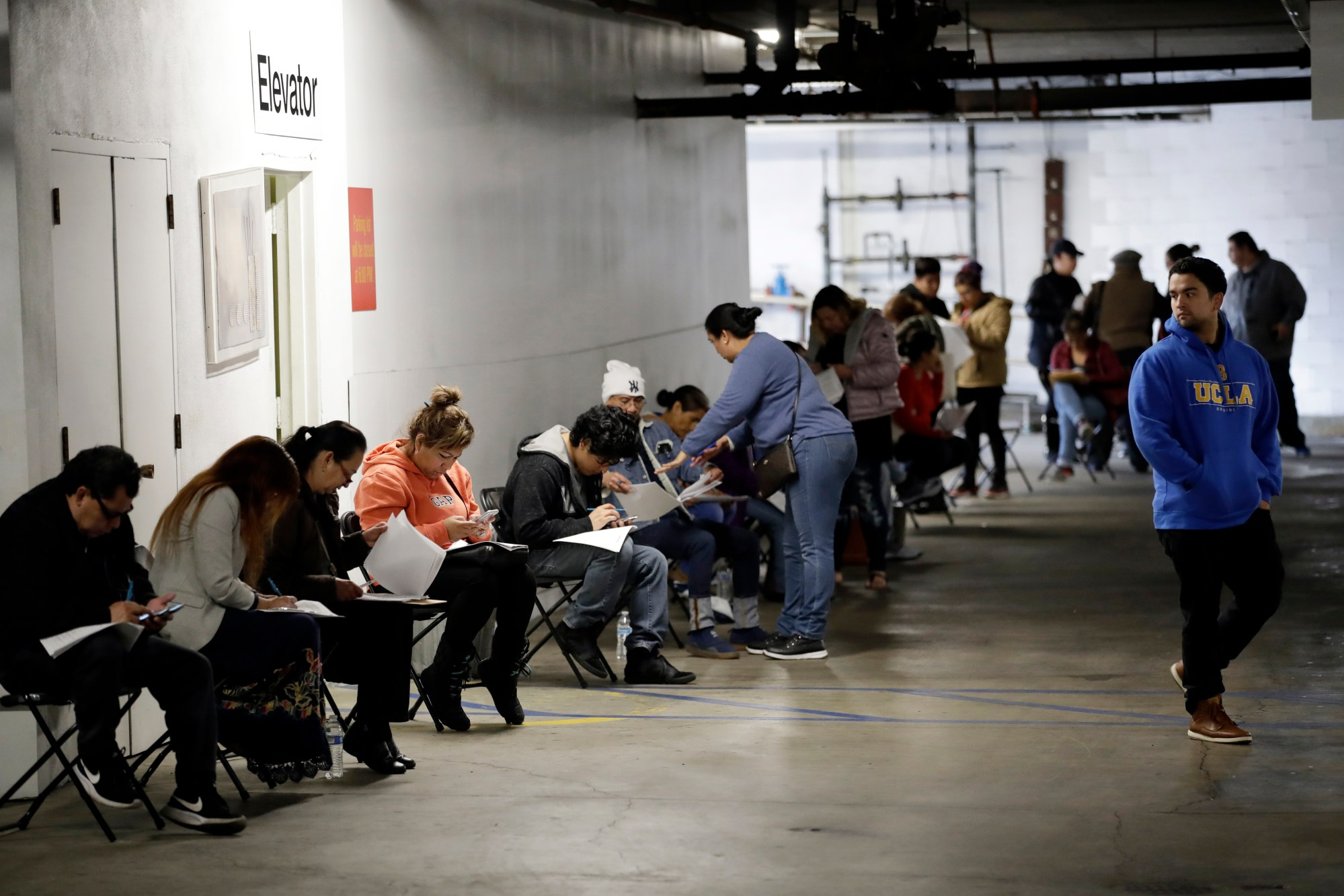In this March 13, 2020 file photo, unionized hospitality workers wait in line in a basement garage to apply for unemployment benefits at the Hospitality Training Academy in Los Angeles. California's unemployment rate continued to climb in May, reaching 16.3% as businesses continued to lay people off because of a state-at-home order aimed at slowing the spread of the coronavirus that has wrecked the state's economy. (AP Photo/Marcio Jose Sanchez, File)