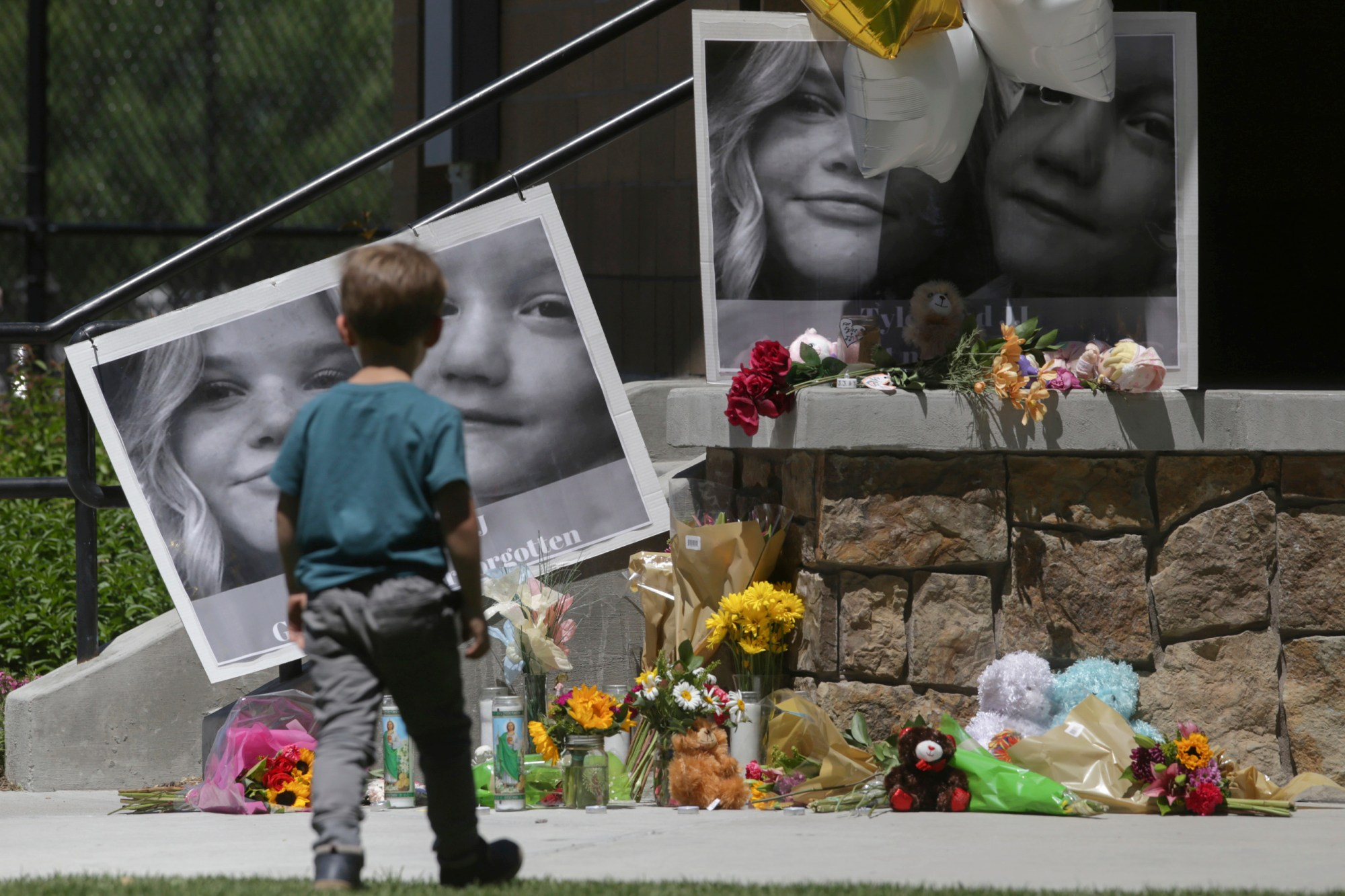 "In this June 11, 2020, file photo, a boy looks at a memorial for Tylee Ryan, 17, and Joshua ""JJ"" Vallow, 7, at Porter Park in Rexburg, Idaho."